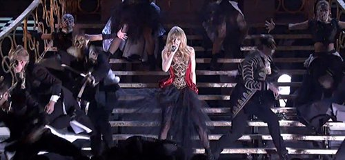 Swift emerges from a pile of people wearing a red and black dress - symbol of sacrifice and initiation.