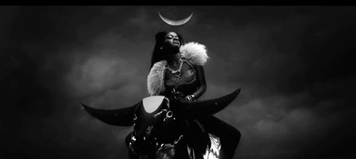 In this scene, Azeala is riding a bull - which represents the masculine energy. Above her is an upright moon crescent, a symbol representing the female principle. The combination of these symbols is basically the union of the opposites through sex magick.