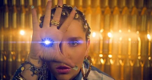 "Ke$ha's video ""Crazy Kids"" features her doing this with an eye on her hand a bunch of times. She appears to do that only when she says ""Crazy Kids"". Listening to the lyrics, the ""Crazy Kids"" are in fact mindless drones listening to insipid pop music."