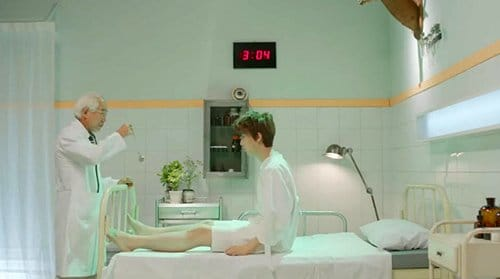 The singer is in a hospital room where he is constantly hypnotized by a creepy handler figure. The clock behind him shows random times, probably noting the fact that MK slaves lose all sense of time. Above the singer is a Baphomet head (we do not fully see it in this shot). This symbolic figure is the anchor point for the slave's alternate worlds.
