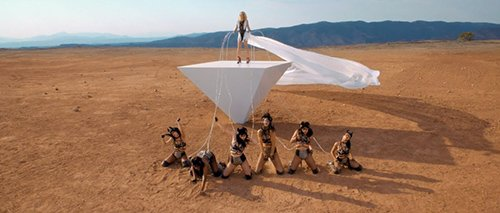 This scene defines the entire video. Britney is holding Beta Kittens on a leash, controlling them. She stands on an inverted pyramid, perhaps to highlight the fact that Britney is actually NOT at the top of the pyramid. She's, in actuality, at the bottom of it, not unlike these leashed kittens.