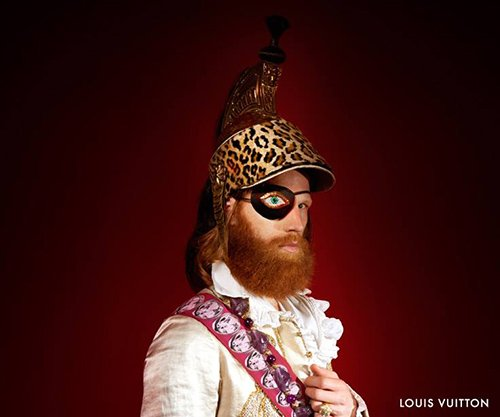"The 2013 fall-winter Louis Vuitton campaign revolves around Venetian masks - à la ""Eyes Wide Shut"". The short video ""Initiation au voyage"" (featuring David Bowie) depicts a ""magical"" venetian masked ball and Louis Vuitton released a series of pics showcasing the guests attire. And guess what: they're full of Illuminati symbolism. In this pic, the guy has an eye patch (hiding one eye). That patch has an eye on it as if to emphasize the one-eye sign."