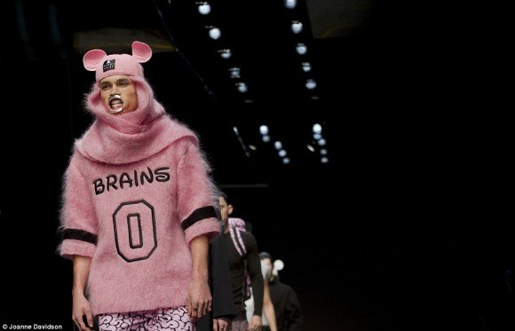 "Speaking of the dehumanizing fashion here are Bobby Abley designs featured at London's Men Fashion Week. Yup, its a guy wearing a shirt saying ""0 brains"", with a Mikey Mouse hat (a symbol of mind control) and a device forcing his mouth open, like some kind of inflatable doll. In short, this model is turned into a brainless, mind controlled zombie. And people are watching this and clapping."