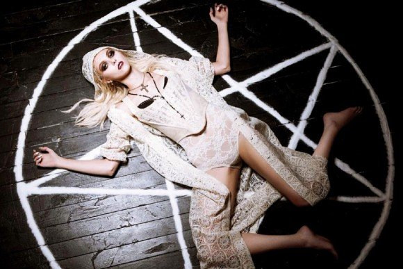 "Here she is laying inside a ""magic circle"" dressed in white as if about to be offered in sacrifice or something. Yup. That's basically what you need to do to be in the music business."