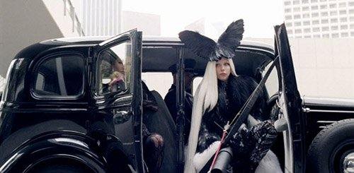 From white, everything now switches to black. Gaga wears crow wings on her head. In Ancient Greece and other civilizations, crows were considered to be omens of death.