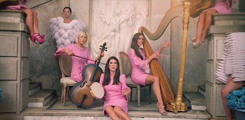 While Gaga's rebirth is happening the Real Housewives of Beverly Hills make an appearance playing musical instruments. The fact that they clearly do not know how to play these instruments and that there's obviously no harp or cello in the actual song add to the fact that this is all about being fake, phony and plastic.