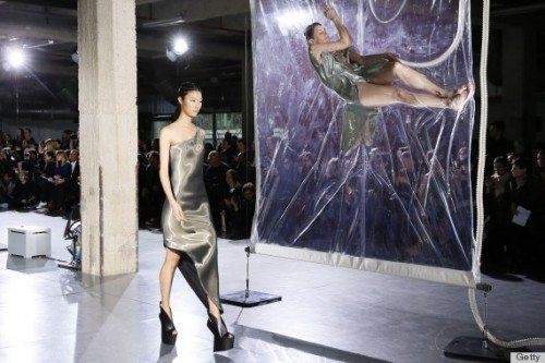 A model walks by as air is slowly being sucked out of the bag next to her. Just another way of adding a disturbing, dehumanizing touch to the fashion world.