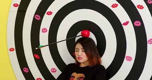 Inspired by the tale of Guillaume Tell, EunB must stand still as an arrow is shot above her head. The arrows form kisses on the target - kisses of death. EunB clearly does not appreciate the exercise, as if she was forced into it.