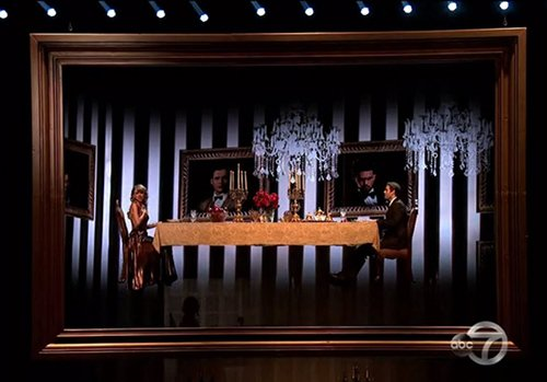 The performance begins with Swift sitting in a classy dining room with some poor sap. Notice the dualistic pattern in the background used in MKULTRA.