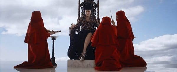 Viktoria sits on a throne while three men in red robes surround her.