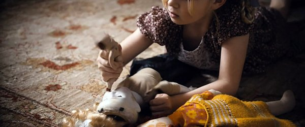 The little girl starts stabbing one of her dolls with the poor figurine's sole leg.