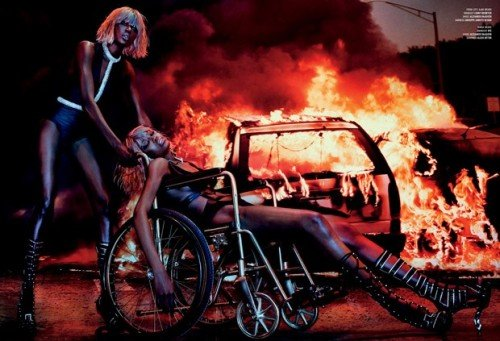 One model in a blond wig pushes an unconscious model with a blond wig while a car is burning in the background. Nothing like juxtaposing the artificial, superficial and dehumanizing fashion world with deep social issues.