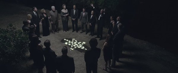 "Gathered around the ritualistic pentagram, these old rich ""respectable"" people keep repeating ""Hail Astraeus"". Sarah appears to be buried underneath the pentagram."