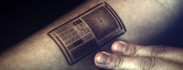 We see a shot of an electronic tattoo embedded with a microchip.