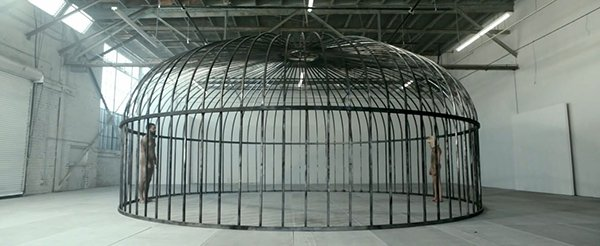 The video begins with Shia and Maddie facing each other inside a giant cage. They are both trapped and, symbolically, both MK slaves.