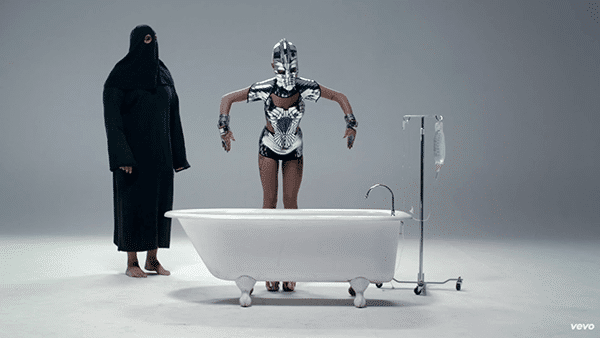 A person wearing a black robe and a mask (the handler?) places Candy, who appears to be paralyzed and unable to move, into a bathtub. There is intravenous equipment next to it, meaning that something awful is about to happen in that tub.