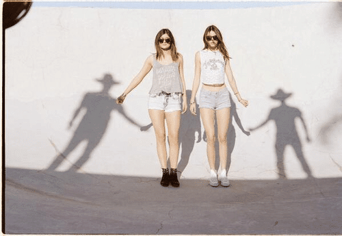 """In this picture, the sisters are holding of two """"shadowy"""" men, which can represents the sinister unseen handlers controlling their lives."""