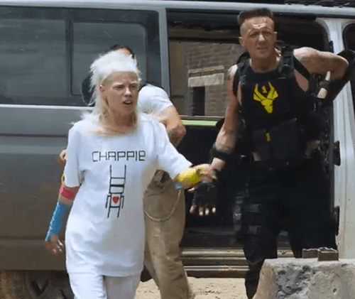 At one point, we see Yolandi walking around with a t-shirt (she apparently made between gun fights) featuring Chappie with a red heart. They are REALLY trying to humanize that robot.
