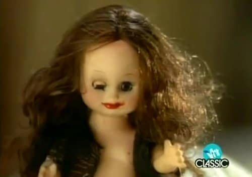 The doll from the beginning of the video. Her hair is messed up, her dress is torn (exposing a breast). One of her eyes is closed - the Illuminati one-eye sign.