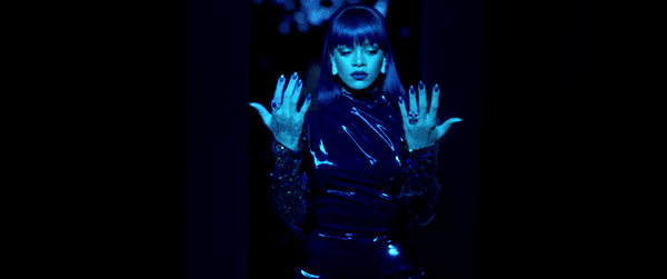 On the other side of the portal, Rihanna is dressed in black, the traditional color of initiation. From her very simple hairstyle and wardrobe, Rihanna is dressed to look like a star, complete with tattoos and an edgy skull ring.