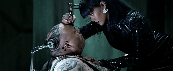Still dressed in black, Rihanna tattooes a guy (who appears to be unable to move) right on the forehead.