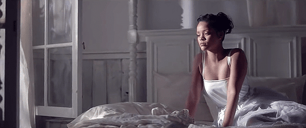In the first room, Rihanna is in an all-white room, dressed in a white dress.