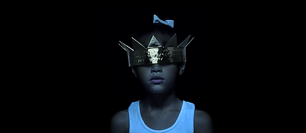 "The two children merge into ""innocent Rihanna"", blinded by the crown she is tool small to properly wear."