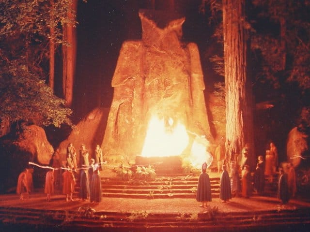 """The Cremnation of Care"" at the Bohemian Grove. The ceremony involves the poling of a small boat across a lake containing an effigy of Care (""Dull Care""). Dark, hooded individuals receive the effigy from the ferryman which is placed on an altar and, at the end of the ceremony, is set on fire."