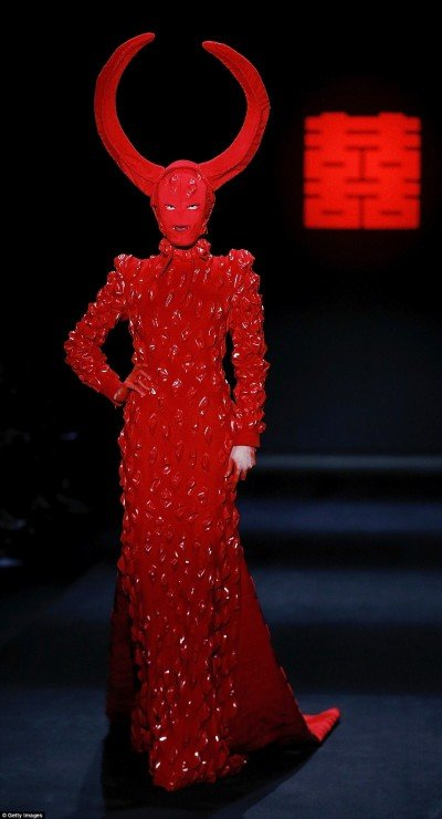The fashion show by Chinese designer Designer Hu Sheguang was all about blood, devils, sacrifice and mind control imagery. In short, it was an unfiltered representation of the occult elite's true face. In this pic, a masked model walking around with gigantic devil horns on her head.