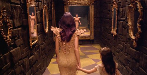 Katy Perry with a young girl (representing her core persona) going through a mirror. Perry's dress is full of butterflies.