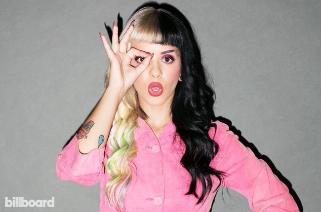 Singer Melanie Martinez was first discovered on The Voice and is now signed with Atlantic Records. Although not a big star yet, she is 100% dedicated to Illuminati and MK symbolism. Here she's doing the one-eye sign in Billboard magazine.