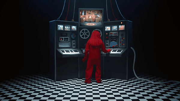 Red Guy finds the console used to unleash the singing things on the friends to program them. Notice that there's a video real and a musical keyboard, hinting that music and video is used to control MK slaves and, on a wider scale, the masses.