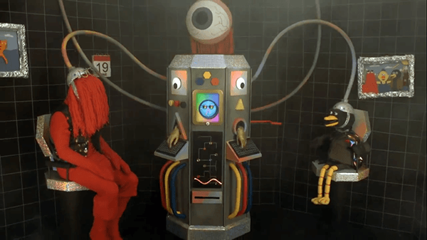 Red Guy and Duck Guy are then seen with their brains connected to a giant computer topped by a giant eyeball. We are starting to understand that the puppets are under litteral mind control.
