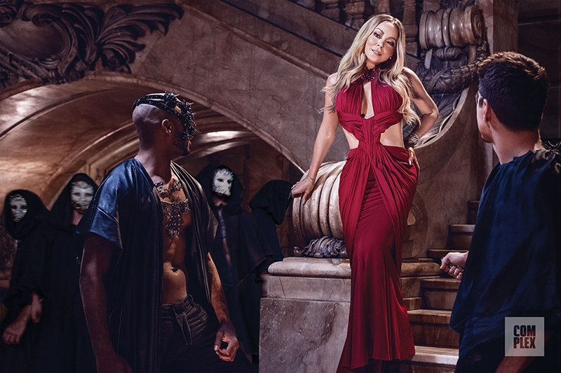"Mariah Carey is on the cover of the August/September issue of Complex in a photoshoot entitled ""Eyes Wide Open"". Not unlike the movie it is inspired from ""Eyes Wide Shut"" (read my article about it here), the photoshoot implies that Mariah is about to partake into an occult sex magick ritual with a bunch of masked men. Her red dress symbolically represents sacrifice."