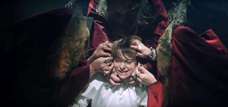 A bunch of witches attach wires to the boy's head.