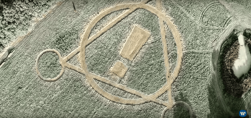 As the camera pans out, we see a crop circle shaped in something resembling an alchemical symbol. The exclamation point is taken from the band's name, indicating that their the one's behind this.