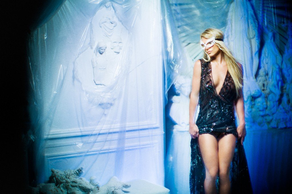"Here she is wearing ""Eyes Wide Shut""-style Sex Kitten mask and dress while standing next to a strange altar containing the Virgin Mary and other figures such as skull heads."