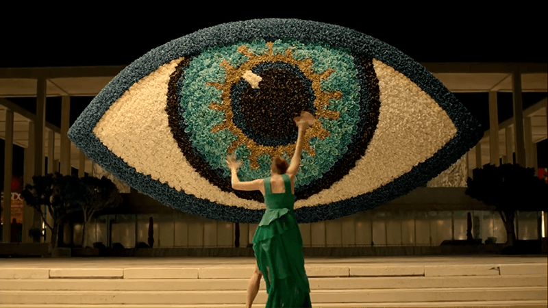 Facing a giant All-Seeing Eye, Margaret wails her arms as if the entity controlling her is forcing her to worship the eye.